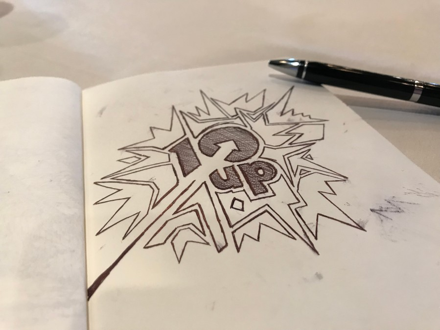Notebook splayed open showing a doodle of the 10up logo and a pen alongside