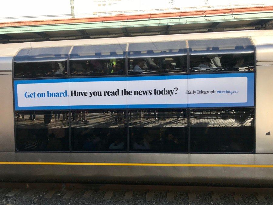 "Photo of train with NewsCorp Australia wrap ad. Text reads, ""Get on board. Have you read the news today?"""