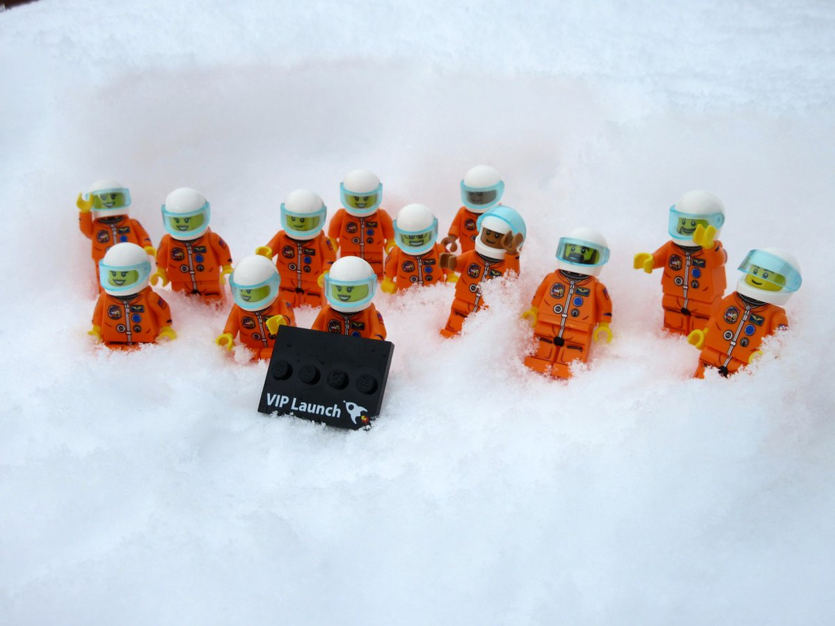 Thirteen Lego astronauts in orange jumpsuits nestled in the snow holding a black sign that reads 'VIP Launch'