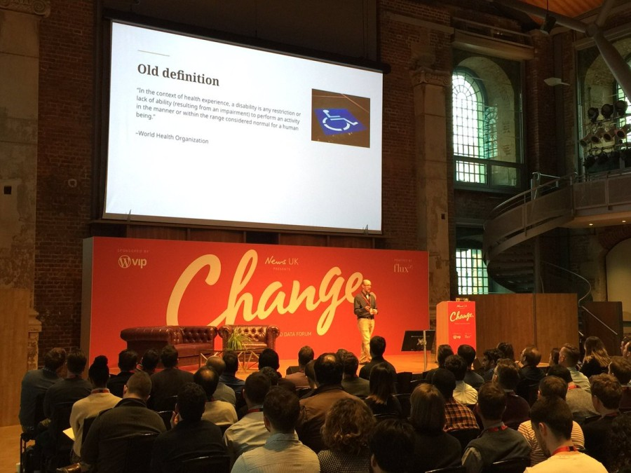 David Kennedy on stage at the Change Forum conference, pictured in front of an audience and against a red background with the word 'Change' inscribed across it.