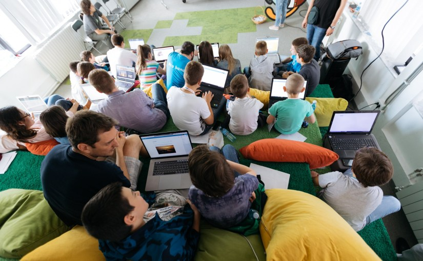 Over a dozen kids with laptops collaborate with WordCamp Belgrade volunteers at one of the first WordCamp kid's workshops