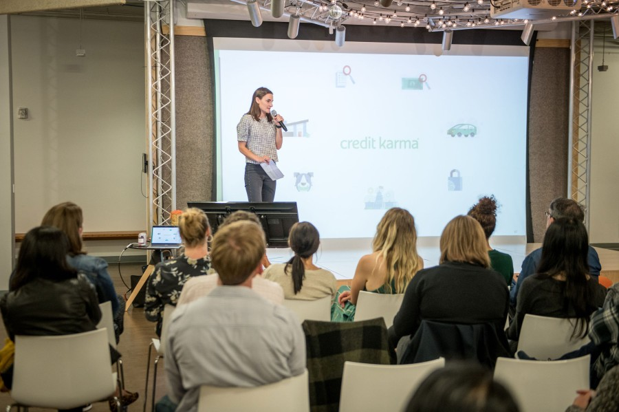 April Aaronson of Credit Karma holds a mic on stage in front of a group of seated people at BigWP SF